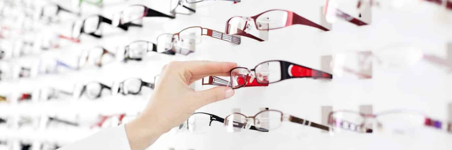 Optician suggest glasses. Closeup showing many eyeglasses in background.